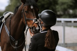 Attractive female equestrian in riding helmet looking at horse in horse club.
