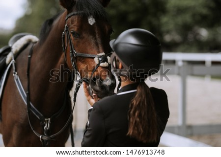 Attractive female equestrian in riding helmet looking at horse in horse club. Сток-фото ©