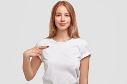 Attractive female in casual white t shirt, indicates at copy space for your logo, isolated over studio wall. Smiling teenage girl advertises new outfit, stands indoor. People, design, clothing concept
