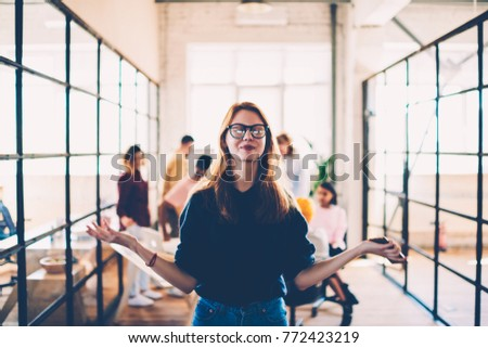 Attractive female in eyeglasses meditating during working process in coworking space finding inspiration, happy young woman with clothes eyes enjoying job with calmness and concentrated on idea