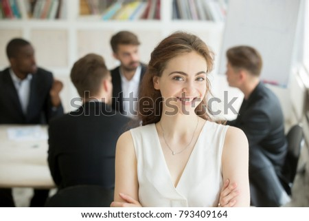 Attractive female leader standing with arms crossed in front of male executive team meeting, smiling businesswoman looking at camera, friendly woman boss, assistant or hr manager headshot portrait