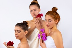 Attractive female models with hair pulled back, wrapped in white towels and holding flowers. Posing on a white background in the studio.