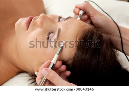 Attractive female patient receiving electro acupuncture on face as part of a anti-aging beauty treatment - stock photo