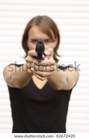 Attractive female pointing a gun.