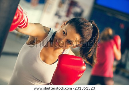 Stock Photo Attractive Female Punching A Bag With Boxing Gloves On