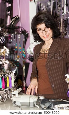 Attractive Female sales clerk behind the cash register