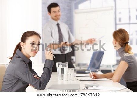 Attractive female sitting at meeting room, listening to presentation.?