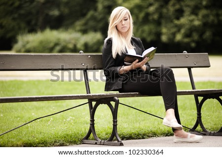 Attractive female sitting in a park with a book
