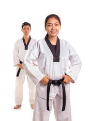 Attractive female tae-kwon-do athlete posing with her male training partner standing behind her, isolated over white background