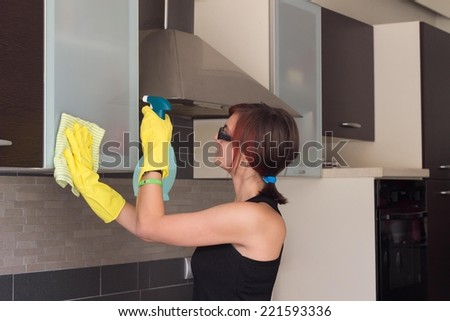 Attractive female teenager cleaning furniture at the kitchen