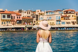 Attractive female tourist looking at the port of Chania, Crete, Greece. Tourist concept. Sightseeing. Summer vacation destination. Travel concept