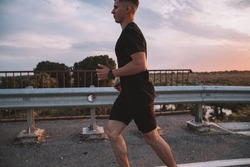 Attractive fit man running along modern bridge at sunset light, man doing workout outdoors, silhouette runner jogging overbridge road with amazing sunset on background