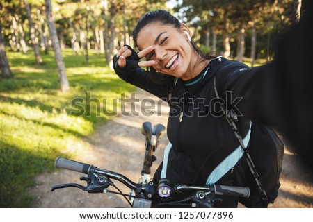 Attractive fit sportswoman riding on a bicycle at the park, listening to music with wireless earphones, taking a selfie