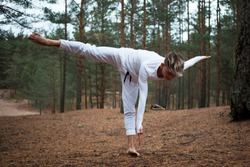 Attractive fit sporty guy with stylish haircut posing in forest doing equilibrium exercise. Athletic young man balancing on one leg, touching feet with opposite hand. Strenth, balance and flexibility