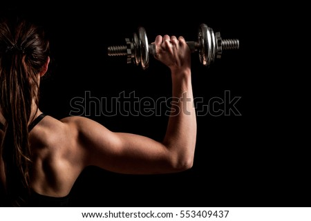 Attractive fit woman works out with dumbbells as a fitness conceptual over dark background.