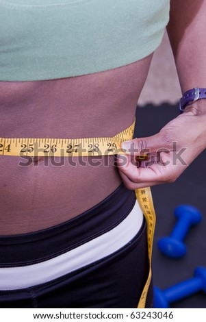 Attractive fitness and workout woman measuring waistline