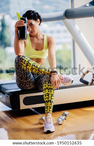 attractive fitness woman tired after workout drinks protein shake.Sexy fitness model resting after workout exercises in gym. fitness exhausted female with protein shaker.  Stock photo ©