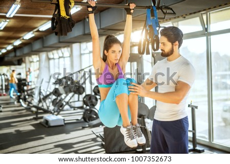 Attractive focused motivated shape active sporty girl doing abs workout with raised legs while holding bar above and personal trainer next to her supporting her in the sunny gym.