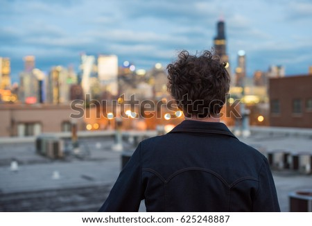 Attractive, forty something man, with long, curly brunette hair, on a rooftop, in the city, with cityscape in the distance. Dusk and sunset lights. Staring into the distance. Contemplating the future.