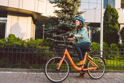 Attractive Friendly Young Woman With Her Bicycle. Portrait of young woman on the street with bicycle. ecological bicycle transport. Student girl came to study at the college on a rental bicycle.
