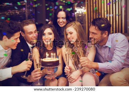 Attractive friends celebrating a birthday against flying colours