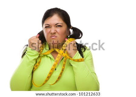 Attractive Frustrated Hispanic Woman Tied Up With Tape Measure Against a White Background.