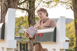 Attractive Full FIgure Woman Reading a Greeting or birthday Card at the Mailbox