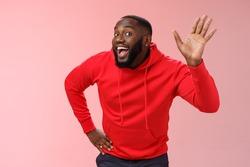 Attractive funny african american gay beard in red hoodie raise palm waving hello hi howdy gesture acting feminine cute fool around welcoming guests greeting standing pink background