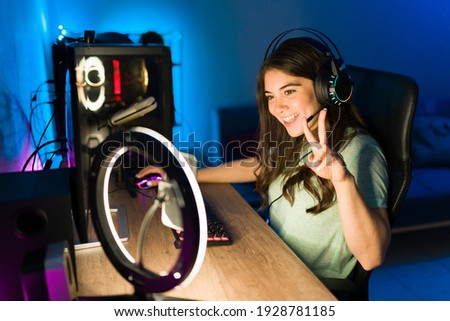 Attractive gamer waving and talking to her viewers during a live stream on her smartphone with a ring light. Young woman playing a videogame on a gaming PC