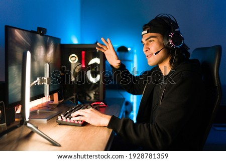 Attractive gamer waving and talking to his friends and viewers during a live stream on a smartphone with a ring light. Young man playing a videogame on a gaming PC Photo stock ©