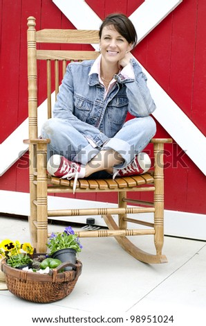 Attractive gardener relaxing after picking flowers and vegetables