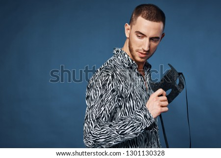 attractive gentleman in a black and white shirt holds a fancy mask in his hand on a gray background