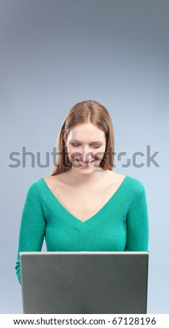 Attractive girl browsing internet, wearing green sweater, smiling