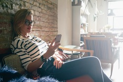 attractive girl chatting with her friends while sitting in a coffee-shop.attractive businesswoman check e-mail on her smart-phone.