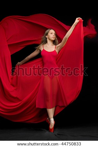 Attractive girl dancer dances in a red dress. - stock photo