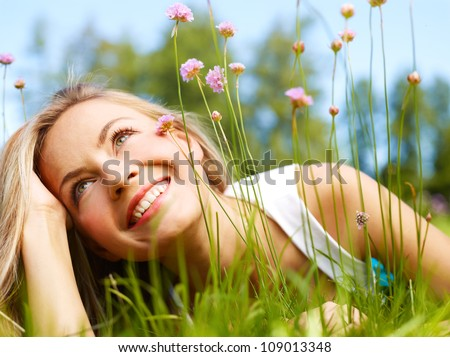 Attractive girl dreaming in a grass with flowers - stock photo