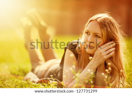 Attractive girl dreaming in a grass with flowers