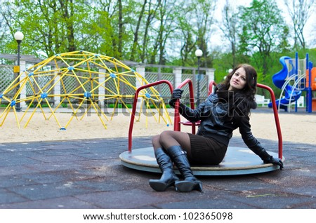 Attractive girl girl in a jacket on the playground
