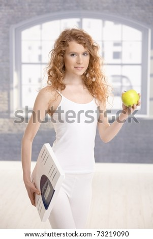 Attractive girl holding apple and scale in hands, living healthy.?
