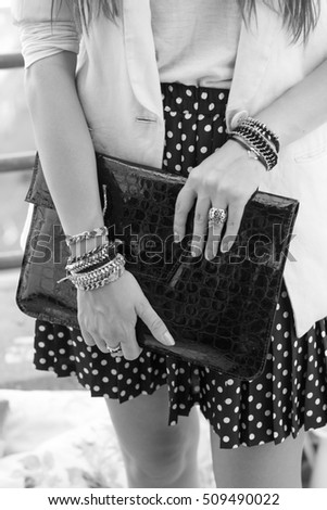 Attractive girl holding purse and wearing hand made jewelry. Black and white theme. #509490022