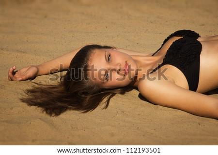 Attractive girl in a bikini on a sandy beach