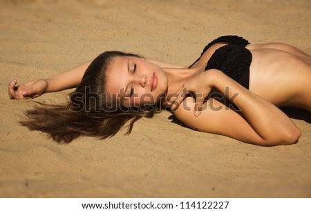 Attractive girl in a bikini relaxing on a sandy beach