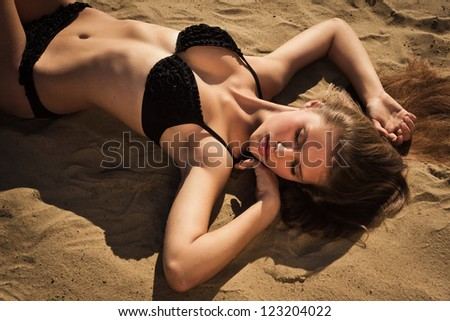 Attractive girl in a bikini relaxing on a sandy beach