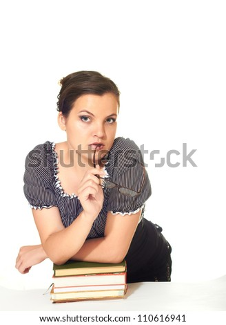 attractive girl in a blouse holds in his right hand points and is leaning on a pile of books isolated on white background