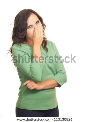 Attractive girl in a green shirt from the stench covers her nose. Isolated on white background