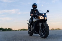 Attractive girl in black leather jacket, pants and helmet on outdoors parking rides on stylish sports motorcycle at sunset.