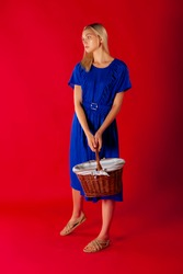 Attractive girl in blue summer dress holding covered basket dreaming looking away.Pretty countryside blond girl in light summer sapphire blue dress holding a wicker basket, posing on a red background.