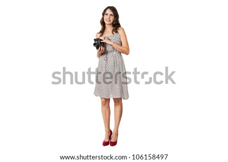 attractive girl in dress holding a vintage film camera isolated on white