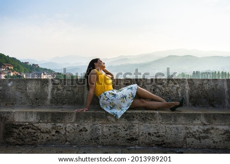 Attractive girl in dress, sitting on old Ottoman bridge in Visegrad, over the Drina River in early morning. Stock photo ©