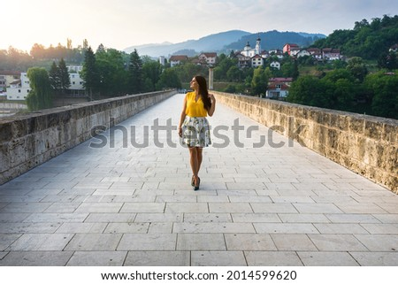 Attractive girl in dress,  standing on old Ottoman bridge in Visegrad, over the Drina River in early morning. Stock photo ©